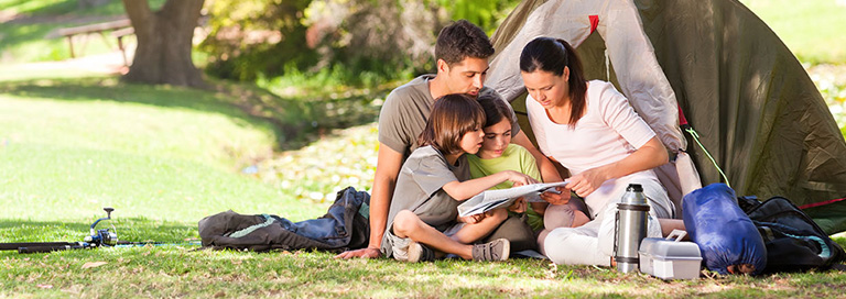 Family reading a map together while camping
